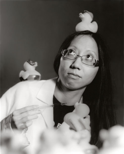 Image of Anita in a lab coat, covered in rubber ducks